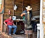 A Cuban farmer roasts fresh coffee beens in a kettle over a wood fire ...near Vinales, Cuba