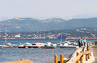 View from Sanary over the sea towards the mainland mountains, Provencal boats moored at buoys in the water, people walking along the water Le Brusc Six Fours Var Cote d'Azur France