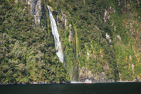 Sightseeing boat under Stirling Falls in Milford Sound, Fiordland National Park, Southland, World Heritage Area, South Island, New Zealand