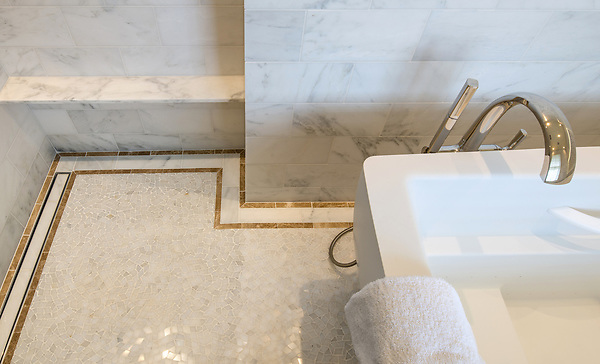 Custom Cosmos floor and border, a hand-cut mosaic shown in polished Afyon White and  Sylvia Gold. Master Bath Design by Meghan Browne.