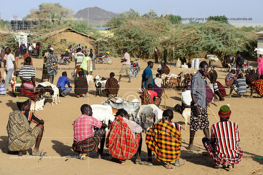KENIA Turkana, Lodwar, cattle market, herder buy and sell goats, man sit on their small wooden chairs / Turkana mit Ziegen auf dem Viehmarkt, Turkana Maenner sitzen auf kleinen Holz Hockern
