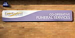 East of England Co-operative funeral services sign on brick wall, Woodbridge, Suffolk, England