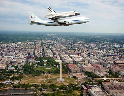 Space shuttle Discovery, mounted atop a NASA 747 Shuttle Carrier Aircraft (SCA), flies over the Washington skyline as seen from a NASA T-38 aircraft, Tuesday, April 17, 2012. Discovery, the first orbiter retired from NASAs shuttle fleet, completed 39 missions, spent 365 days in space, orbited the Earth 5,830 times, and traveled 148,221,675 miles. NASA will transfer Discovery to the National Air and Space Museum to begin its new mission to commemorate past achievements in space and to educate and inspire future generations of explorers. .Mandatory Credit: Robert Markowitz / NASA via CNP