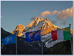 Choose the Right Foreground.<br /> To photograph Mt Marmolada at sunset seems pretty obvious. Afterwards, look for some well-lit foreground like these flags. When your foreground is a dark object, it must produce a strong silhouette or it will blend into the background. <br /> Dolomites in northeast Italy.