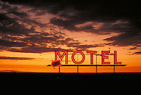 A red neon motel sign is seen at sunset. Coulee City Washington.