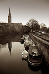 Narrow boats on the river Avon in Bath, Somerset, England with calm water and church spire in distance during winter