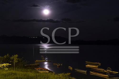 Altamira, Para State, Brazil. Xingu river by moonlight with wooden voadeira boats.