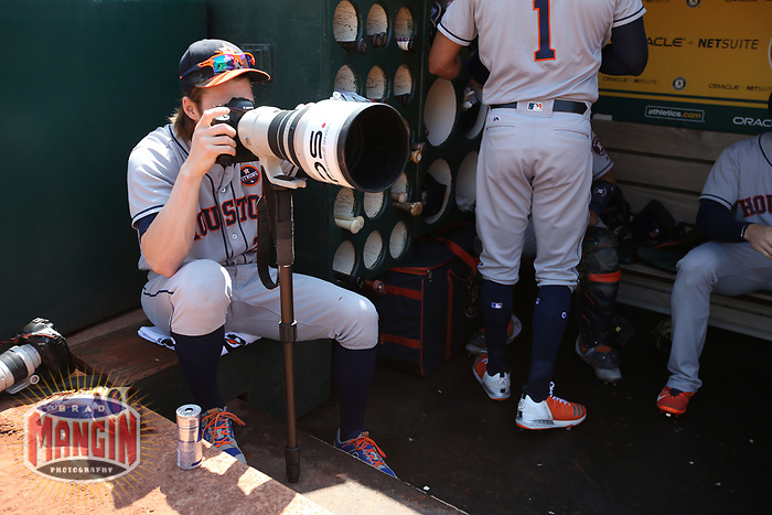 OAKLAND, CA - SEPTEMBER 9:  Josh Reddick #22 of the Houston Astros takes pictures with a Canon camera belonging to Oakland A's team photographer Michael Zagaris in the dugout before game 1 of a doubleheader against the Oakland Athletics at the Oakland Coliseum on Saturday, September 9, 2017 in Oakland, California. (Photo by Brad Mangin)