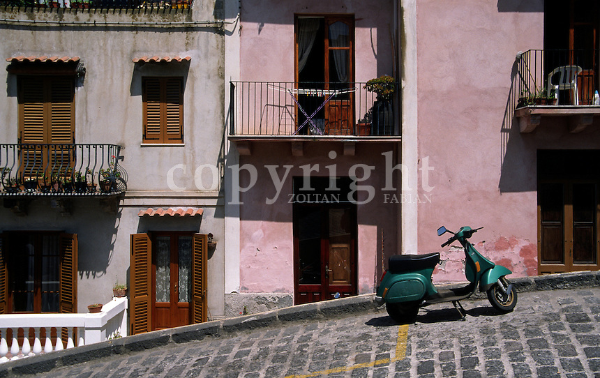 Scooter parking on a steep street next to mediterranean houses on Lipar island, Italy, Europe