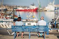 """Im Hafen der Sizilianischen Kleinstadt Porto Empedocle wurden die Rettungsschiffe """"Sea-Watch 3"""" und """"Ocean Viking"""" der privaten Seenotrettungsorganisationen Sea-Watch und SOS Mediterranee, von der italienische Küstenwache im Juli 2020 festgesetzt. Zuvor hatten die Organisationen mit den beiden Schiffen mehrere hundert Menschen vor der libyschen Kueste aus Seenot gerettet. Die italienischen Behoerden versuchen mit der offiziellen Begruendung, """"Sicherheitsmaengel"""", weitere Rettungseinsaetze zu blockieren.<br /> Im Bild: Ein Paar betrachtet die Ocean Viking (rotes Schiff) und die Sea-Watch 3 (blaues Schiff, links).<br /> 25.7.2020, Porto Empedocle<br /> Copyright: Christian-Ditsch.de<br /> NUR FUER REDAKTIONELLE ZWECKE! Werbung nur auf Anfrage beim Fotografen. [Inhaltsveraendernde Manipulation des Fotos nur nach ausdruecklicher Genehmigung des Fotografen. Vereinbarungen ueber Abtretung von Persoenlichkeitsrechten/Model Release der abgebildeten Person/Personen liegen nicht vor. NO MODEL RELEASE! Don't publish without copyright Christian-Ditsch.de, Veroeffentlichung nur mit Fotografennennung, sowie gegen Honorar, MwSt. und Beleg. Konto: I N G - D i B a, IBAN DE58500105175400192269, BIC INGDDEFFXXX, Kontakt: post@christian-ditsch.de<br /> Bei der Bearbeitung der Dateiinformationen darf die Urheberkennzeichnung in den EXIF- und  IPTC-Daten nicht entfernt werden, diese sind in digitalen Medien nach §95c UrhG rechtlich geschuetzt. Der Urhebervermerk wird gemaess §13 UrhG verlangt.]"""