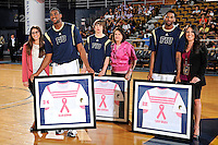 25 February 2012:  FIU's Joey De La Rosa (34) presents a jersey to Ellen Durman (also pictured, Tanner Wozniak (23) and Brandon Moore (22)) during a ceremony honoring cancer survivors prior to the game.  The FIU Golden Panthers defeated the University of South Alabama Jaguars, 81-74, at the U.S. Century Bank Arena in Miami, Florida.