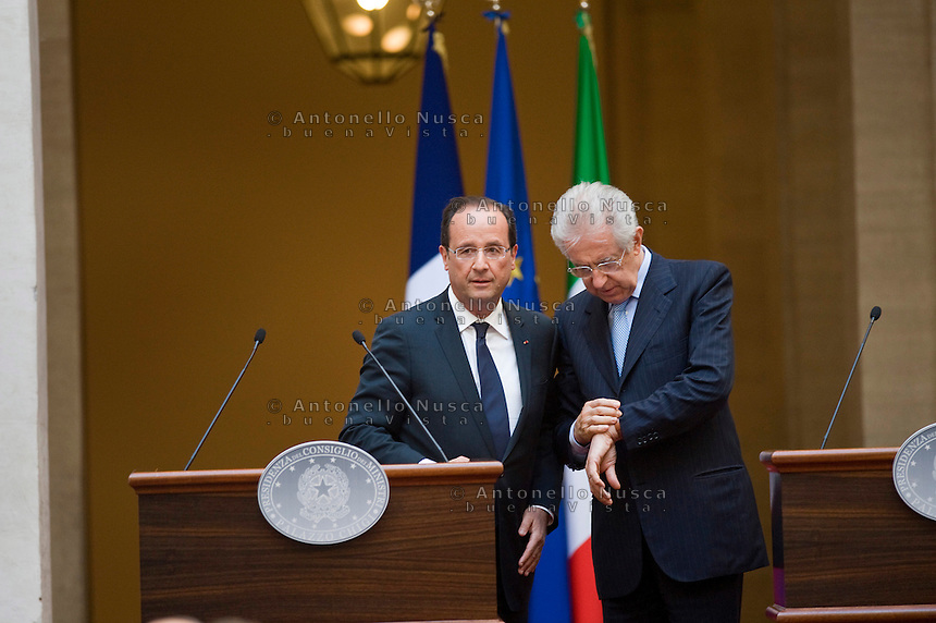 Il Presidente Francese Francois Hollande e Mario Monti durante la conferenza stampa a Palazzo Chigi dopo il loro incontro..France's President Francois Hollande (L) and the Italian Prime Minister Mario Monti check the time at the end of a joint press conference following their meeting at palazzo Chigi in Rome.