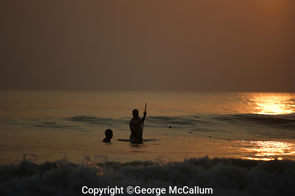 Pair of Beach fishermen pulling one end of Gill net through surf, Goa, Arabian sea, India.
