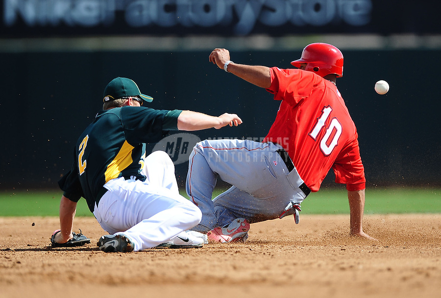 Mar. 4, 2012; Phoenix, AZ, USA; Los Angeles Angels base runner (10) Vernon Wells slides safely into second base with a stolen base as Oakland Athletics shortstop (2) Cliff Pennington fields the ball in the first inning during a spring training game at Phoenix Municipal Stadium.  Mandatory Credit: Mark J. Rebilas-
