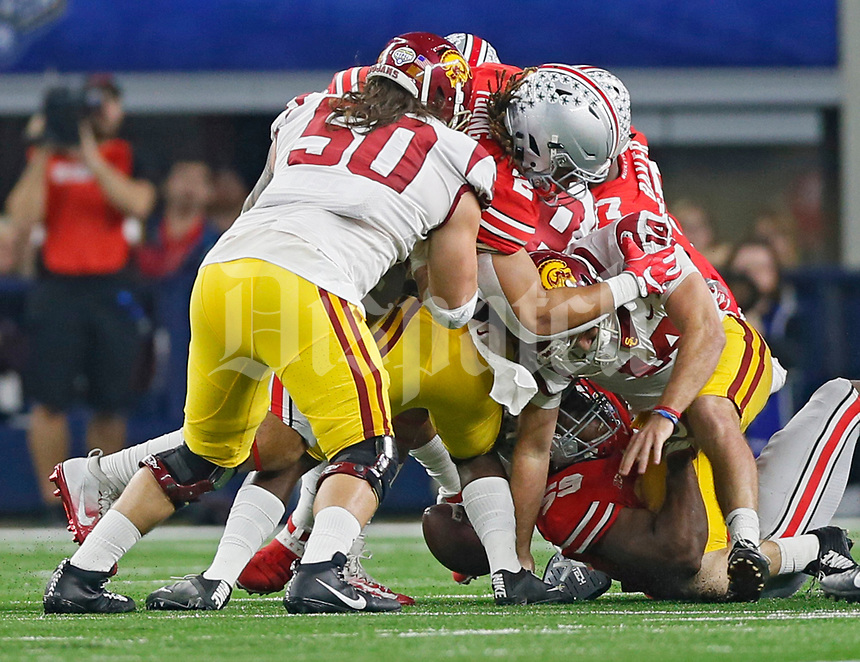 Ohio State Buckeyes defensive lineman Tyquan Lewis (59) strips the ball from USC Trojans quarterback Sam Darnold (14) for a fumble that Ohio State Buckeyes recovered during the 1st half at the 82nd Goodyear Cotton Bowl Classic at AT&T Stadium in Arlington, Texas on December 29, 2017.  [Kyle Robertson/Dispatch]
