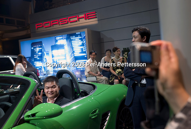 SHANGHAI, CHINA OCTOBER 10: An affluent Chinese man sits in a green Porsche at a stand at the yearly Millionaires Fair on October 10, 2008 in Shanghai, China. About fifty exhibitors showed their luxury goods such as jewelry, cars, property, kitchens and many other must haves for the newly rich. China has a growing number of millionaires and about 320,000 of them are estimated to live in Mainland China. The Chinese are currently the third-largest consumer of luxury goods, behind Japan and the United States. (Photo by Per-Anders Pettersson/Getty Images)...