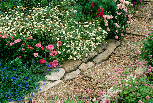 Pastel garden in bloom with pathway made of aggregate block pavers and lined with limestone