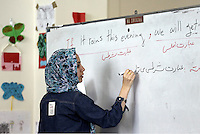 Pictured: The english language teacher writes on the board Monday 06 February 2017<br /> Re: A school teaching the English language has been operating at the migrant camp located in the former airport in the outskirts of Athens, Greece.