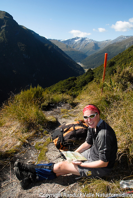 Jente ser på kart,  Mt. Aspiring nasjonalpark. ---- Girl looking at map, Waterfall Face, Mt. Aspiring National Park.