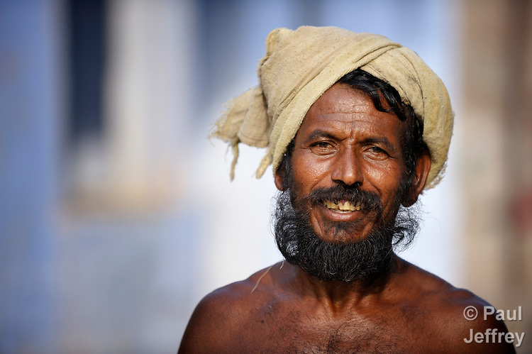 A man smiles on a street in Sathangudi, a village in the southern Indian state of Tamil Nadu.