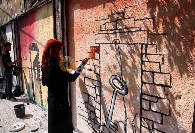 Palestinian artists put the final touches to graffiti on a wall in Gaza City on May 06, 2010. The phrase is Arabic reads ?we will definitely come back?. US envoy George Mitchell was to meet with Israel's Benjamin Netanyahu for a second time in a bid to lay the groundwork for the opening of indirect peace talks with the Palestinians. Photo by Mohammed Asad