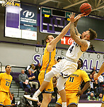SIOUX FALLS, SD - DECEMBER 7: 	Trevon Evans #4 from the University of Sioux Falls shoots over the defense of Max Keefe #32 from Concordia St. Paul during their game Friday night at the Stewart Center in Sioux Falls, SD. (Photo by Dave Eggen/Inertia)