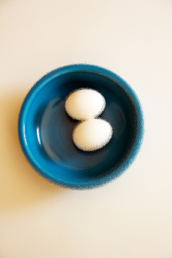 Bright blue bowl with 2 white eggs on white background