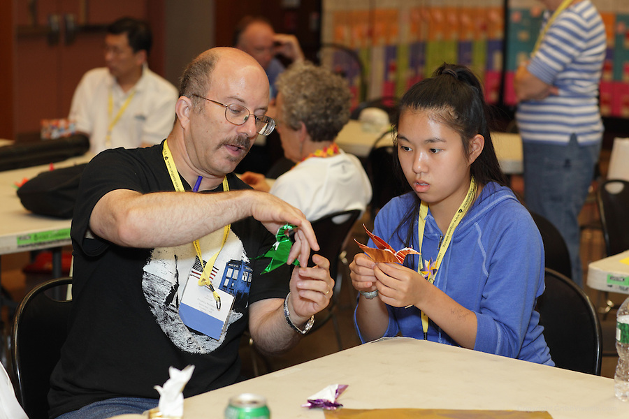 New York, NY, USA - June 23, 2012: Bob Voelker teaches an origami friend how to fold a special model between classes. The OrigamiUSA 2012 Convention held at Fashion Institute of Technology, New York, attracts members from the USA with visitors from Asia, the Americas, and Europe. Attendees exhibit their work and take part in classes, and an exhibition of big folding.