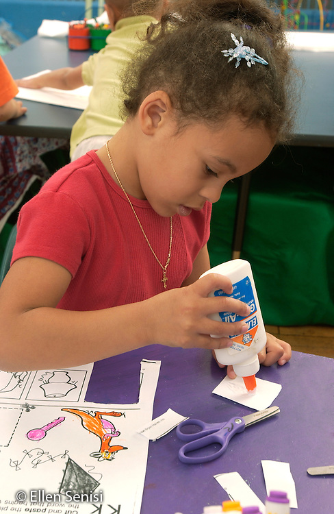 """MR / Schenectady, NY.Yates Arts-in-Education Magnet School.Full-Day Pre-K class; urban school.State Funded through NYS Universal Pre-K Program.Girl (4, African-American) finishing reading readiness worksheet on the letter """"K"""" squeezes glue.  Completing the worksheet has required her to use eye hand coordination, visual recognition, and phonics skills to select, color, cut, and paste objects..MR: Cag4.©Ellen B. Senisi"""