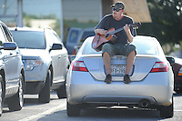 NWA Democrat-Gazette/ANDY SHUPE<br /> Max Green of Dallas plays guitar Thursday, Sept. 10, 2015, while sitting atop his car in a parking lot in south Fayetteville. Green was passing time while his friend was inside a business as the two travel through the area.
