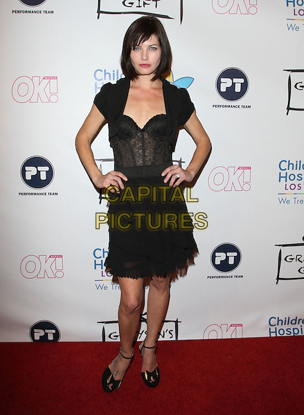 DELPHINE CHANEAC.CHLA'S 1st Annual Grayson's Gift Foundation held at Casa Del Mar Hotel, Santa Monica, CA, USA..November 11th, 2010.full length dress lace corset skirt jacket cropped hands on hips ankle strap shoes black.CAP/ADM/FS.©Faye Sadou/AdMedia/Capital Pictures.