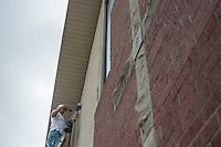 NWA Democrat-Gazette/ANTHONY REYES • @NWATONYR<br /> Mike Brown, with David Mabry Building Inc. of Lowell, paints the stucco Wednesday, Sept. 9, 2015 in front of the First Baptist Church in Lowell. Brown has been working on remodeling inside and outside the church for a few weeks.