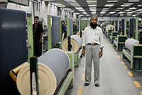 BANGLADESH , textile industry in Dhaka , textile factory Beximco produce Jeans for export for western discounter, fabric weaving department / Bangladesch , Textilbetrieb Beximco in Dhaka produziert Jeans fuer den Export fuer westliche Textildiscounter, maschinen zum Weben der Jeansstoffe