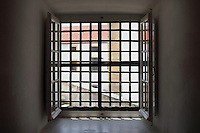 Window covered with iron bars, in the University Prison, with iron door, in use 1541-1834, of which 2 staircases remain, in the Joanina Library, or Biblioteca Joanina, a Baroque library built 1717-28 by Gaspar Ferreira, part of the University of Coimbra General Library, in Coimbra, Portugal. This is the only existing medieval prison in Portugal. The Casa da Livraria was built during the reign of King John V or Joao V, and consists of the Green Room, Red Room and Black Room, with 250,000 books dating from the 16th - 18th centuries. The library is part of the Faculty of Law and the University is housed in the buildings of the Royal Palace of Coimbra. The building is classified as a national monument and UNESCO World Heritage Site. Picture by Manuel Cohen