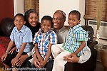 portrait of family parents with sons ages 8, 6, and 3 years old sitting on couch at home Muslim American African American horizontal