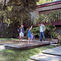 David and Elizabeth Netto and their two daughters relaxing in the shallow reflecting pool adjacent to the house