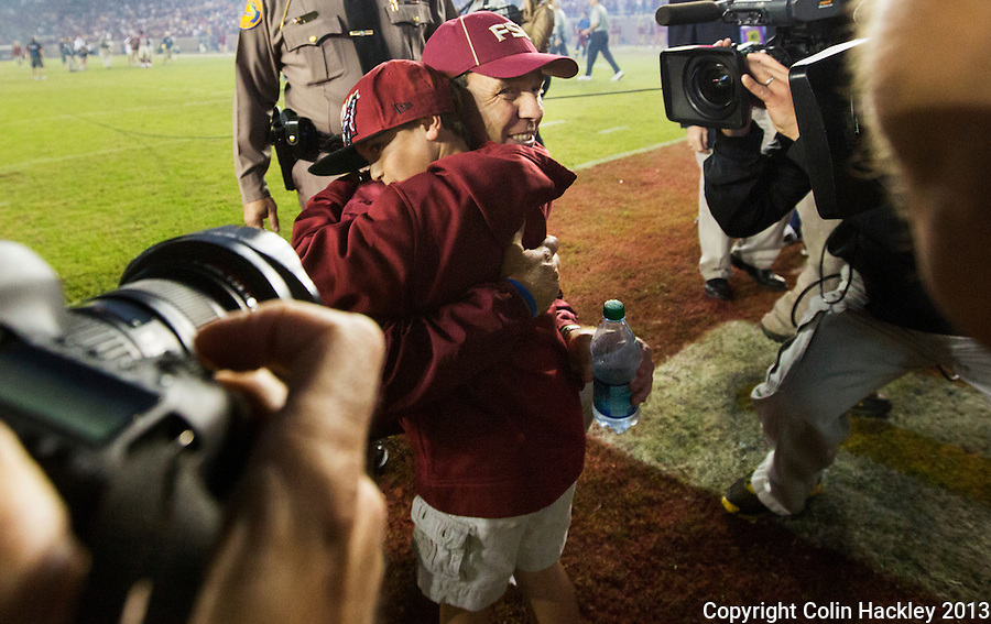 TALLAHASSEE, FL 11/2/13-FSU-MIAMI110213CH-Florida State Head Coach Jimbo Fisher hugs his son Ethan after the Miami game Saturday at Doak Campbell Stadium in Tallahassee. The Seminoles beat the Hurricanes 41-14.<br /> COLIN HACKLEY PHOTO