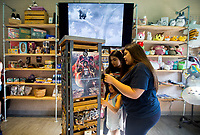 NWA Democrat-Gazette/JASON IVESTER<br /> Stephanie Barnes (from left), 15, Juliane Barnes, 7, and Carmina Halbert, 18, all of Rogers, look over items Thursday, May 25, 2017, during an open house for Anime Cafe in downtown Rogers.