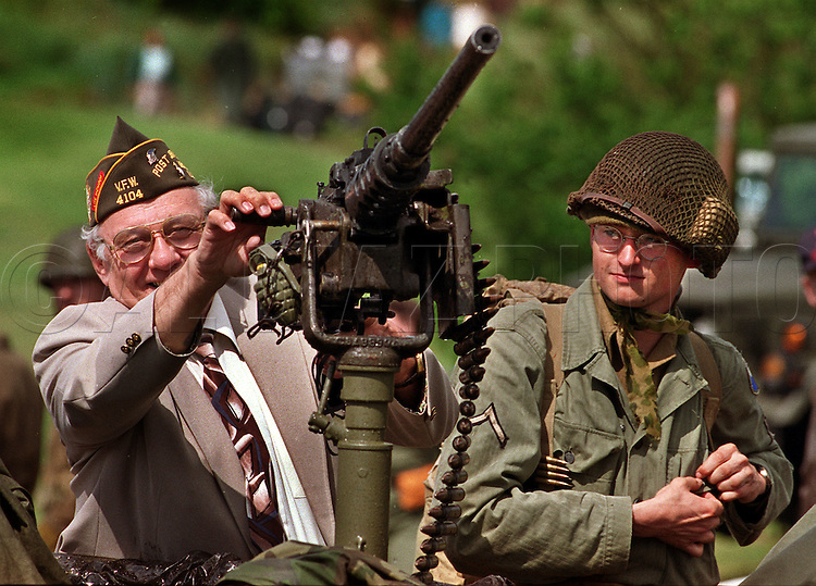 A D-Day veteran checks out an M2 Browning 50 caliber machine gun mounted on a WWII vintage jeep at Normandy. The American GI re-enactor at right is German.
