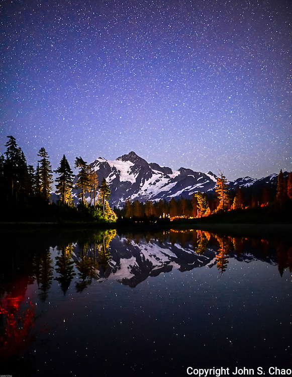 Mount Shuksan under a starry night sky reflected in Picture Lake, with trees lit by passing car's headlights. North Cascades National Park and Mount Baker - Snoqualmie National Forest, respectively.