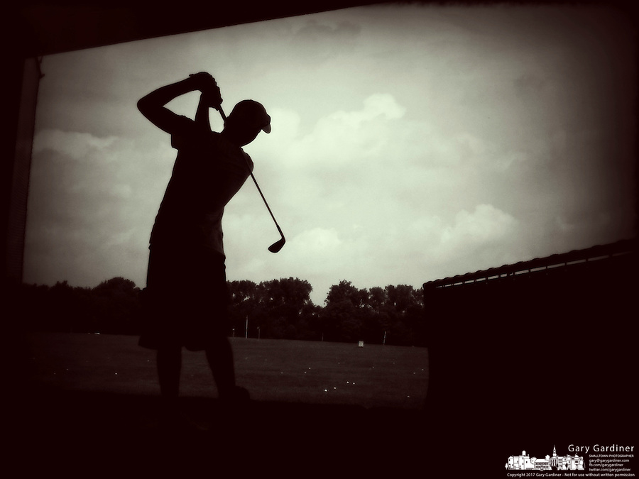 Golfer silhouetted against the sky at driving range. iPhone photo