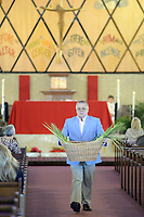 A Knights of Columbus member, who declined to identify himself, carries palm leaves to the back of the church for distribution to parish members at St. Michael the Archangel Catholic Church after Palm Sunday services Sunday April 9, 2017 in Levittown, Pennsylvania. Palm Sunday commemorates Jesus' triumphal entry into Jerusalem. (Photo by William Thomas Cain)
