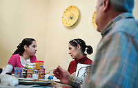 John Woodard (cq), his wife, Martha Woodard (cq), and their daughter Ashley Woodard (cq, age 11) eat dinner at home in Laredo, Texas, US, Thursday, Dec. 10, 2009. Because of the slumping economy, John is looking into getting another job to make ends meet. Martha, a native Spanish speaker from Mexico, is learning English, in part, to help take over managing their apartment business and be able to answer phone calls in English. Martha also wants to learn English to be able to help her children with homework, which is always in English...PHOTOS/ MATT NAGER