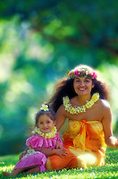 A beautiful Polynesian woman with her daughter, in colorful aloha wear and wearing plumeria and haku leis, sit together on the grass. Muted green foliage background.