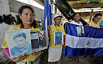 Maria de Jesus Silva Velasquez (left) and other women hold photos of their disappeared family members during a December 18, 2013 demonstration on the banks of the Suchiate River that forms much of the border between Guatemala and Mexico. The women crossed the river from Mexico to hold their demonstration in Tecun Uman, Guatemala.<br /> <br /> These women, all from Nicaragua, were part of a caravan of 45 people from Central America who spent 17 days touring 14 Mexican states in search of their loved ones, most of whom had disappeared while following the migrant trail north. In addition to searching for clues to the fate of their loved ones, they called on the Mexican government to improve its treatment of migrants transiting the country.<br /> <br /> Silva holds photos of her daughter Jacqueline Silva Giron, who was kidnapped by traffickers in 2004 at the age of 11. Silva has identified the woman responsible for her daughter's kidnapping, but has been unable to locate her daughter for nine years. The second photo she holds is of her nephew Humberto Mayorga Silva, who left in 2007 when he went to search for Silva's daughter. He last called in 2011 but hasn't been heard from since.