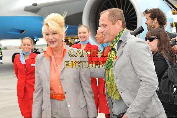 IVANA TRUMP & GERY KESZLER.Arrival at the airport for Life Ball, Vienna, Austria..May 15th, 2009.half length jacket orange shirt green scarf profile grey gray .CAP/PPG/ECK.© Eckharter/People Picture/Capital Pictures