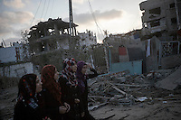 "In this Friday, Aug. 15, 2014 photo, Palestinian women walk by house buildings destroyed by israeli airstrikes and artillery shelling during the ""Protective Edge"" military operation in Al-Khobar area in Gaza City. After a five days truce was declared on 13th August between Hamas and Israel, civilian population went back to what remains from their houses and goods in Gaza Strip. (Photo/Narciso Contreras)"