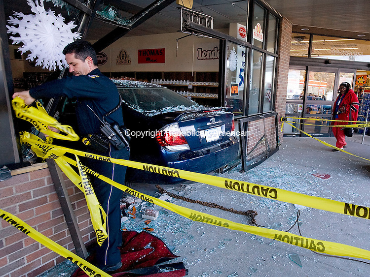 WATERBURY--31 January 07--013108TJ03 - Waterbury police officer Lee Santos, left, ties up caution tape around the entrance to Freihofer's Bakery Outlet after a car drove in to the storefront at 649 West Main Street in Waterbury on Thursday, January 31, 2008. Waterbury resident Bertha Wiley looks on at right. (T.J. Kirkpatrick/Republican-American)