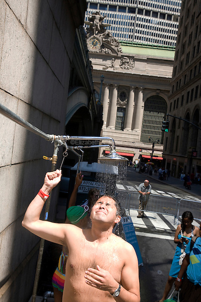"A man showers after ""dumpster diving"" in swimming pools made out of dumpsters on Park Avenue near Grand Central Station on 07 August 2010.  People were allowed 20-minute turns swimming in any of the three ""dumpster pools."""