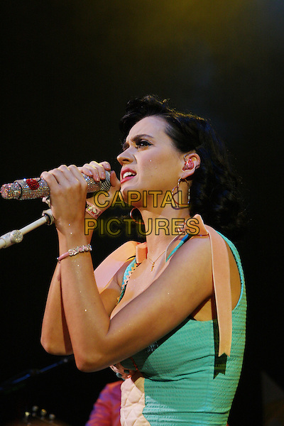 KATY PERRY.Performing live at the Shepherd's Bush Empire, London, England..June 9th, 2009.stage gig performance music half length blue green teal top playsuit jumpsuit singing profile jewel encrusted microphone bracelets orange ribbon bow .CAP/MAR.© Martin Harris/Capital Pictures.